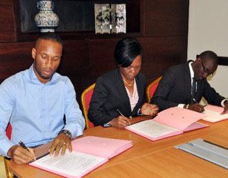 Didier Drogba (left) signing the gold mine purchase documents next to Cote d'Ivoire's Economy and Finance junior minister Niale Kaba (centre) and Ivorian Budget junior minister Abdourahmane Cisse. PHOTO | AFP