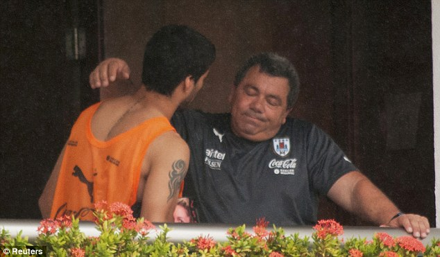 Little comfort: Suarez was seen embracing a member of coaching staff on a balcony at the team's hotel.