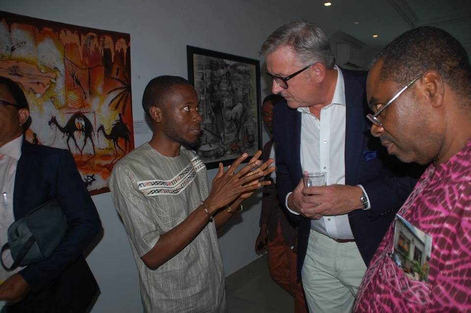 Spanish Embassy Visual Competition winner Sor Sen engaging an art enthusiast in discussion