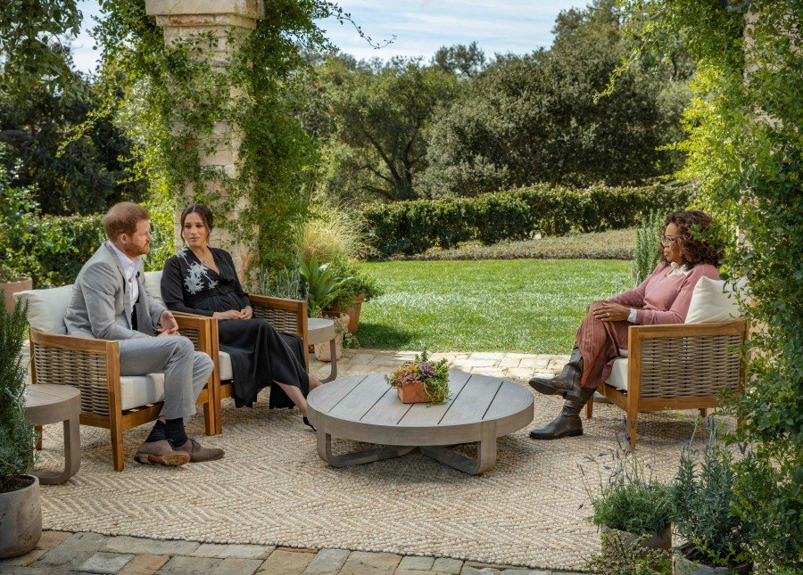 This undated image released March 7, 2021 courtesy of Harpo Productions shows Britain's Prince Harry (L) and his wife Meghan (C), Duchess of Sussex, in a conversation with US television host Oprah Winfrey. AFP/ HARPO PRODUCTIONS